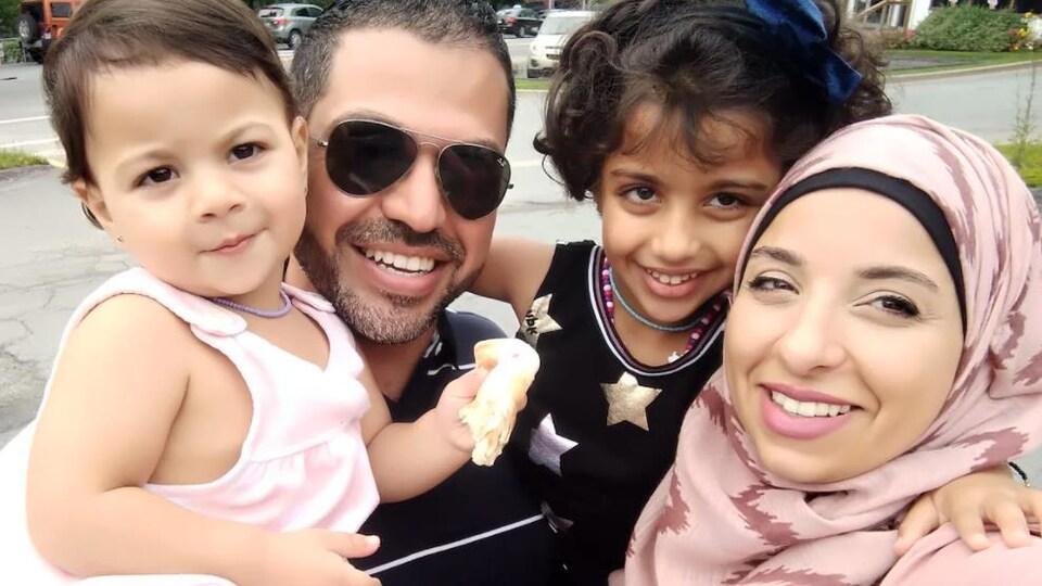 Un homme et une femme souriants tiennent deux fillettes dans leurs bras.