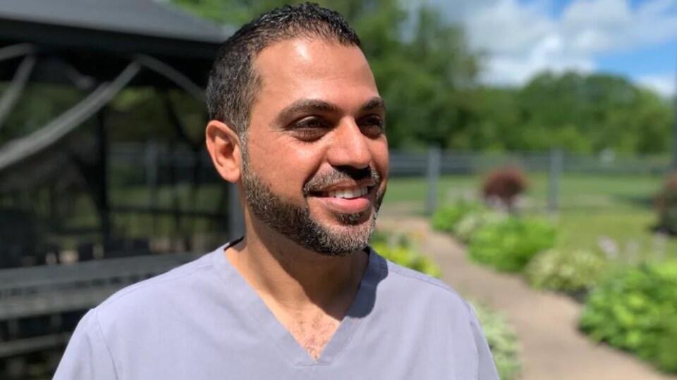 Un homme souriant en uniforme dans un jardin extérieur, sous le soleil.