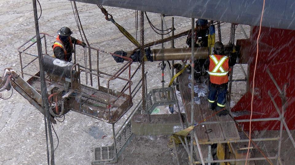 Des mécaniciens travaillent sous le navire.