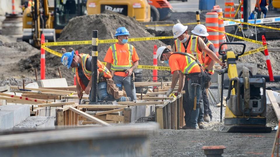 Des travailleurs de la construction s'affairent sur un chantier.