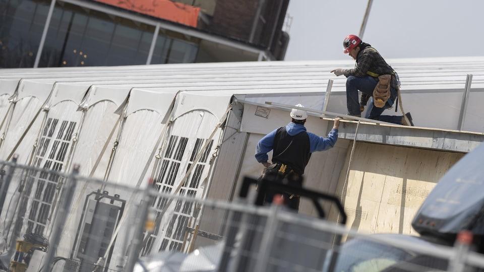 Deux ouvriers juchés près d'un chapiteau.