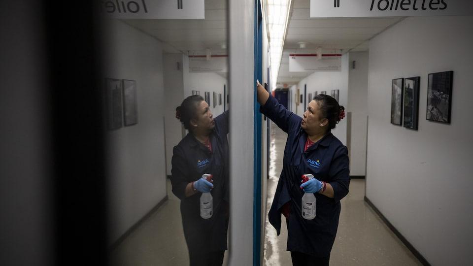 Une concierge nettoie une vitre dans un couloir.