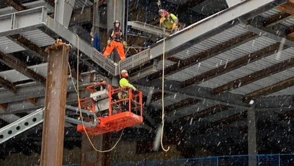 Trois ouvriers travaillent sur un étage élevé dénudé de murs d'un immeuble en construction situé sur la rue Georgia au centre-ville de Vancouver.