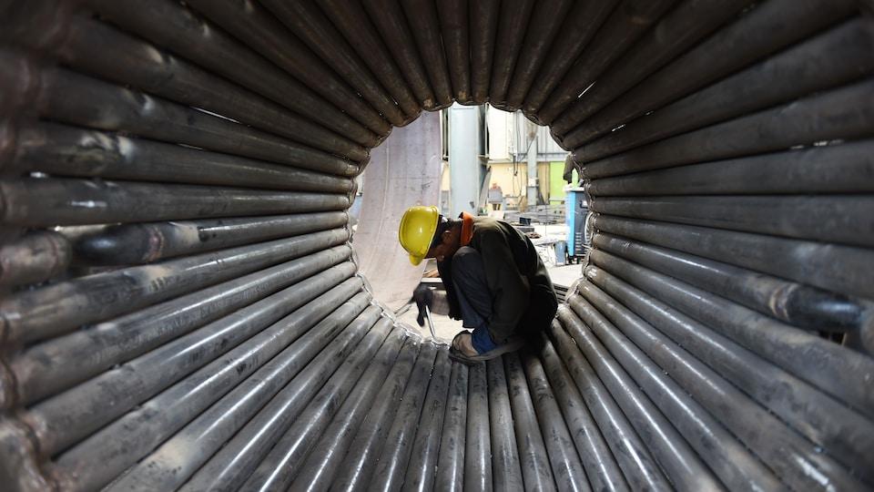 Un travailleur s'affaire dans une structure métallique.