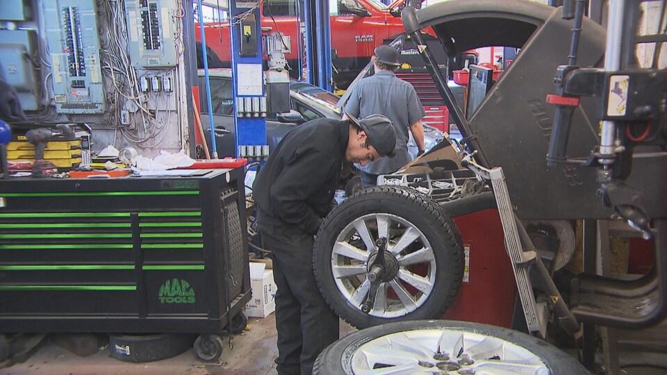 Deux jeunes qui travaillent dans un garage.
