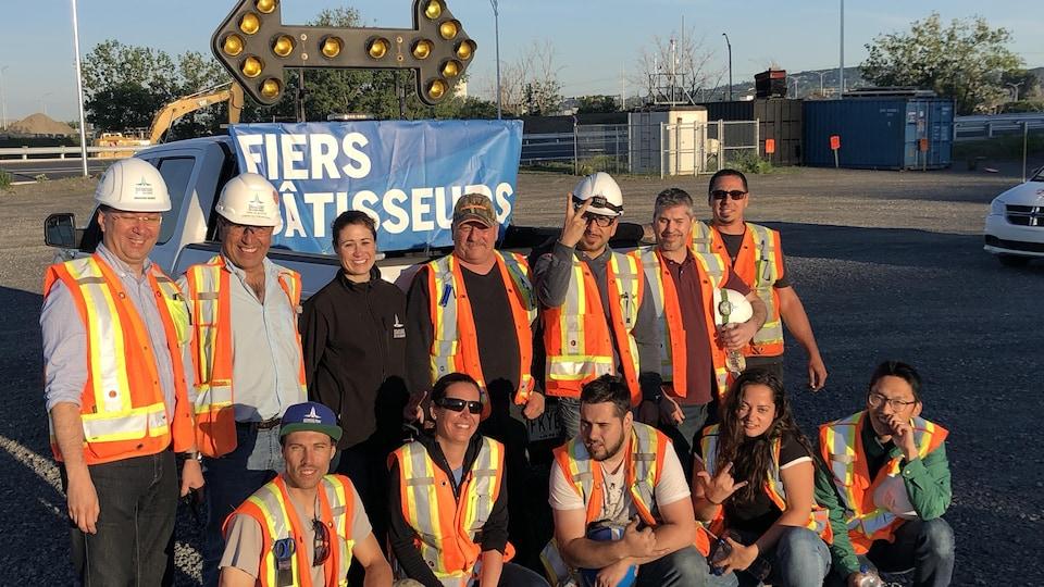 Une douzaine de travailleurs posent devant un camion.