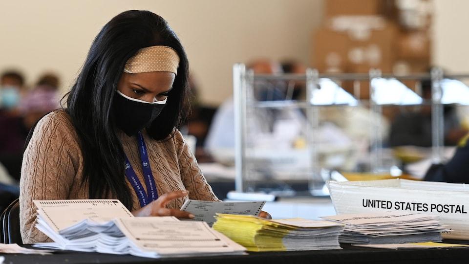 Une travailleuse d'un bureau électoral étudie un bulletin de vote postal.