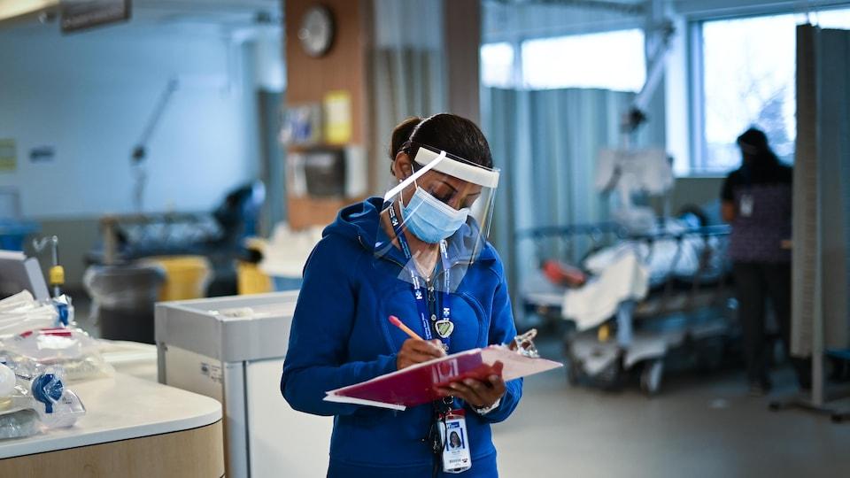 Une infirmière habillée en bleu et portant un masque et une visière prend des notes alors qu'elle se tient debout dans une salle d'hôpital.
