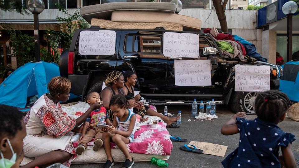 Des femmes et des enfants assis sur un matelas sur la bord d'une route.