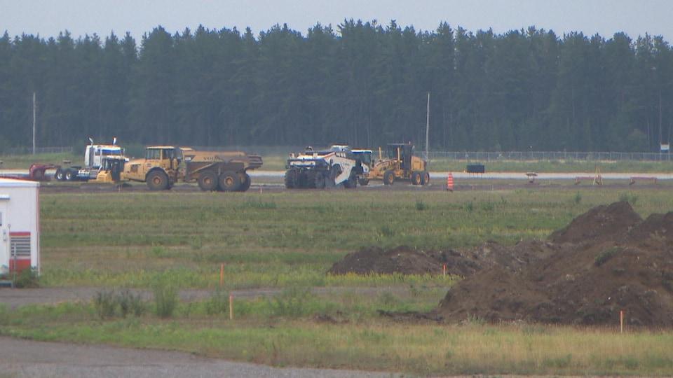 Des machines travaillent sur la piste de l'aéroport.