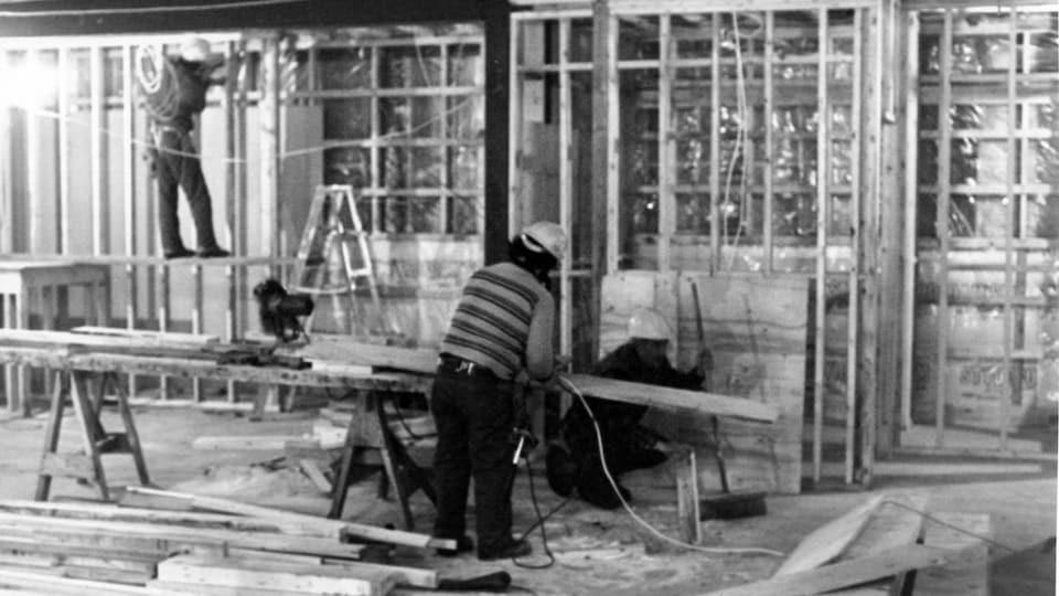Photo d'archives en noir et blanc. Deux hommes font des travaux de menuiserie.
