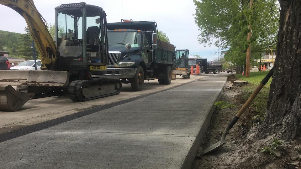 Des véhicules de pavage et d'asphaltage près d'un trottoir fraîchement fait.