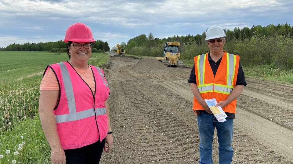 Chantal Poliquin et Jacques Grenier portant des vestes réfléchissantes et un casque dur sur un chantier routier.