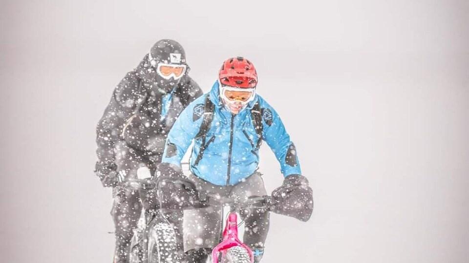 Deux cyclistes dans la neige.