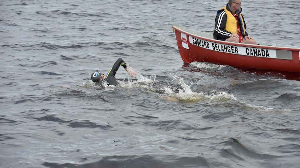 Un homme nage avec une barque à côté de lui.