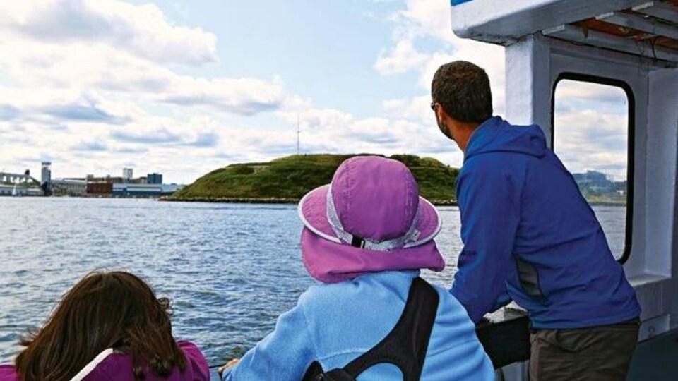 Un homme, une femme et une fille sont sur un bateau au large de l'île Georges.