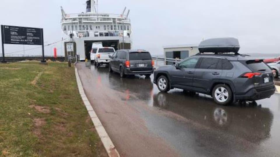 Quatre voitures font la queue pour monter à bord du traversier