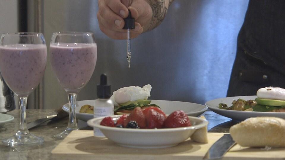 Le chef fait tomber quelques gouttes de THC sur une assiette remplie d'un brunch à côté d'une assiette de fruit et de deux verres à vin remplis de smoothie violet.