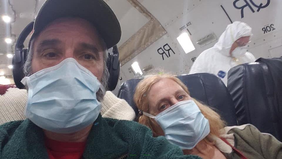 Mike Zrobin portant un masque assis dans l'avion.