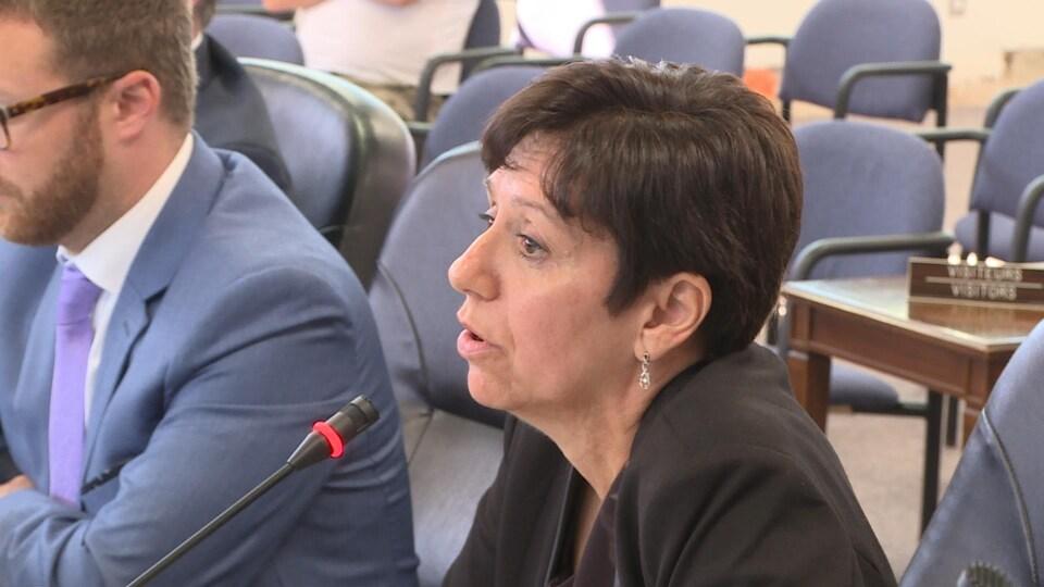 Une femme parle devant un micro