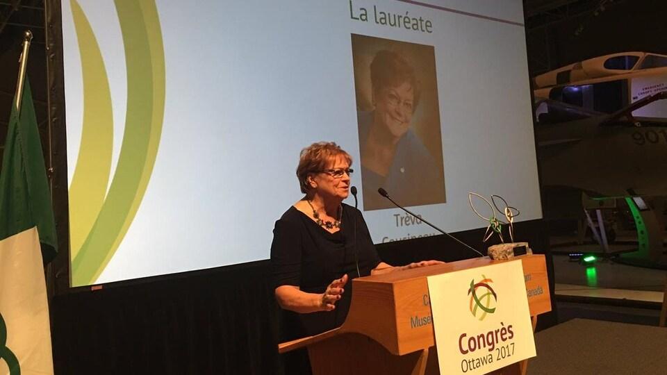 Trèva Cousineau à un pupitre devant une assemblée.