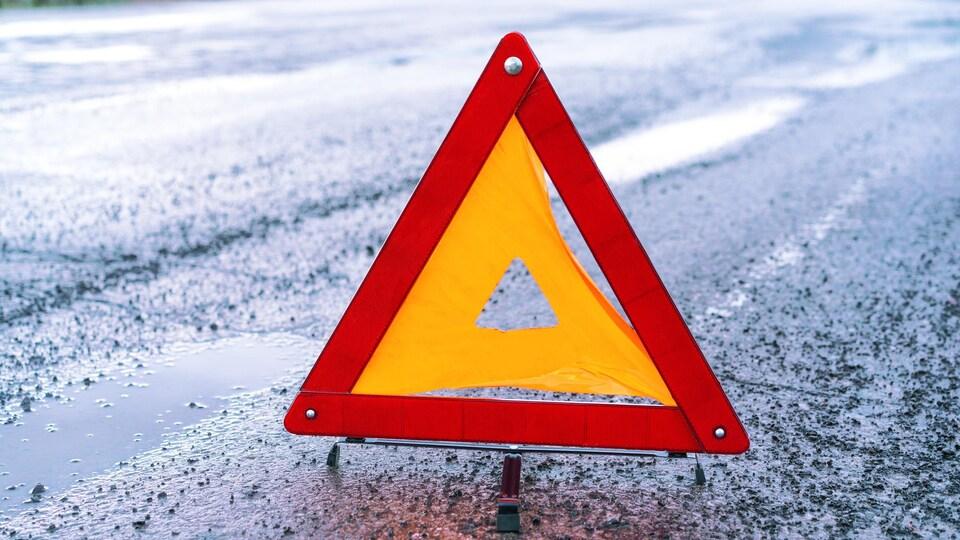 Un triangle sur la chaussée mouillée qui invite à la prudence.