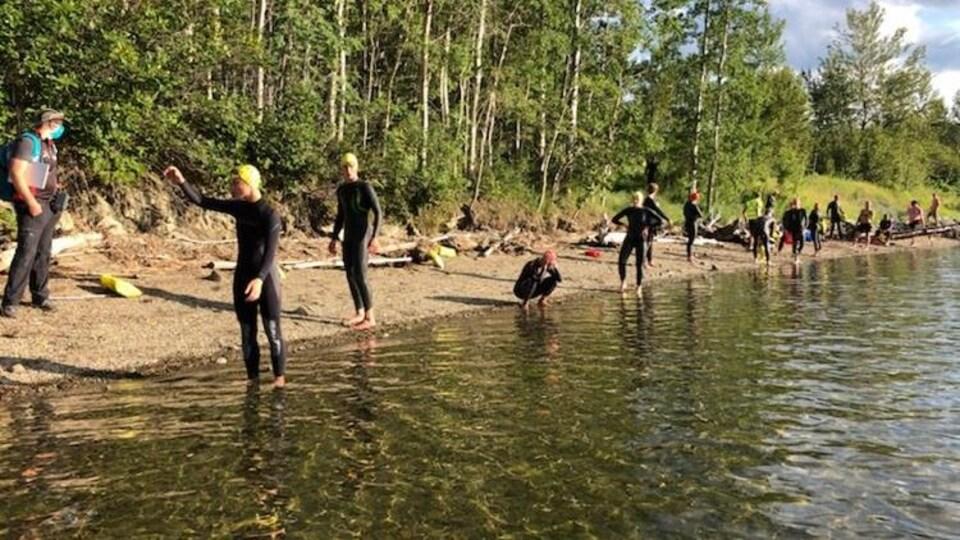 Les participants du triathlon de Gaspé en ligne sur le bord de la baie en attendant le départ.