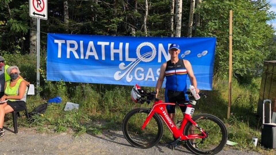Jean-René Hamel, premier au sprint, pose avec son vélo devant la bannière du triathlon de Gaspé.