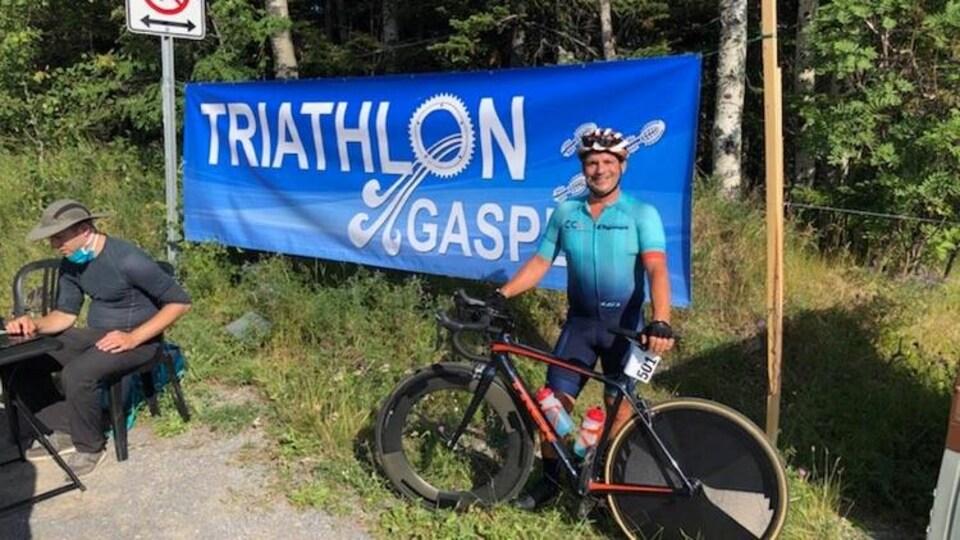 André Côté, premier à l'épreuve olympique de vélo, pose devant la bannière du triathlon de Gaspé.