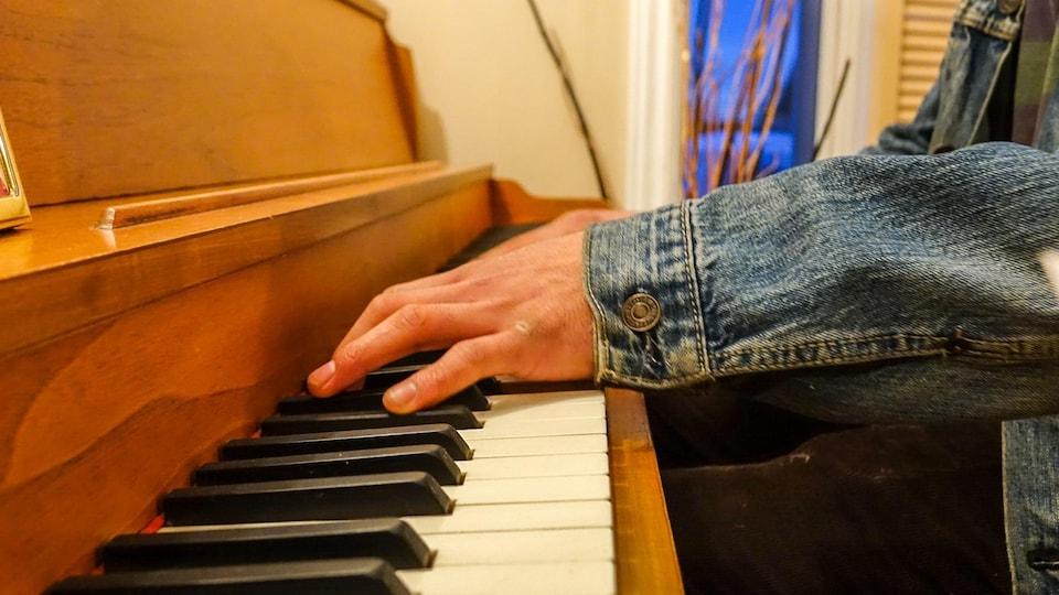 Un jeune homme photographié de manière anonyme joue du piano