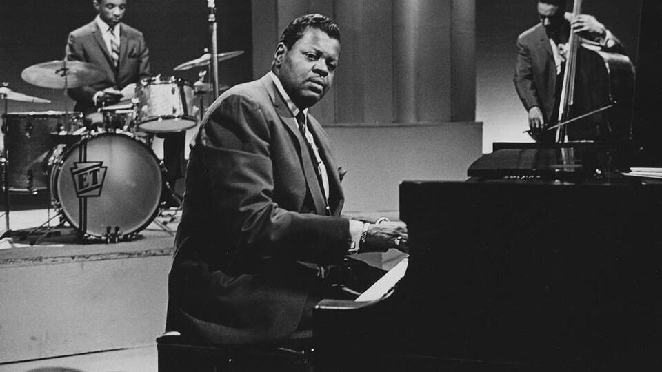 Dans un studio de télévision, Oscar Peterson, assis au piano, avec en arrière-plan Ed Thigpen à la batterie et Ray Brown à la contrebasse.