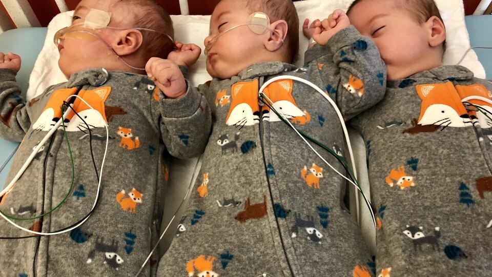 Photo des triplés Nathan, Logan et Félix. Les enfants dorment sur le dos dans une couchette.