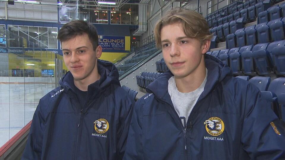 Deux jeunes hommes en manteau devant des estrades d'aréna.