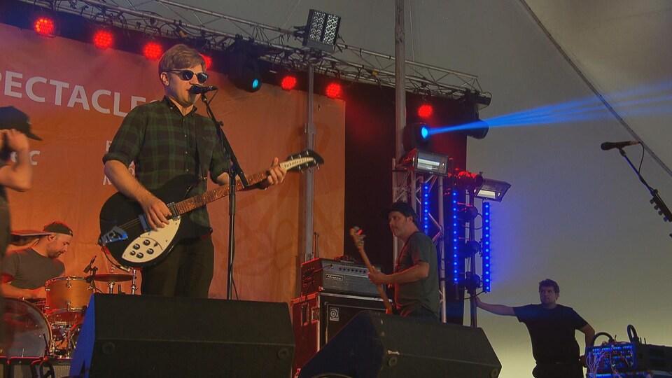 Le chanteur du groupe au micro avec sa guitare. Des musiciens jouent à l'Arrière.