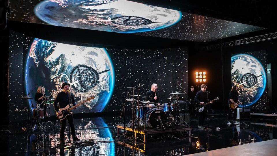 Cinq musiciens sur scène, entourés d'un écran incurvé géant montrant des images de l'espace.