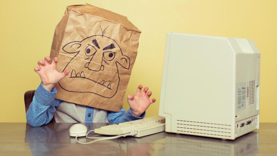 Un enfant, un sac sur la tête, menace un vieil ordinateur.
