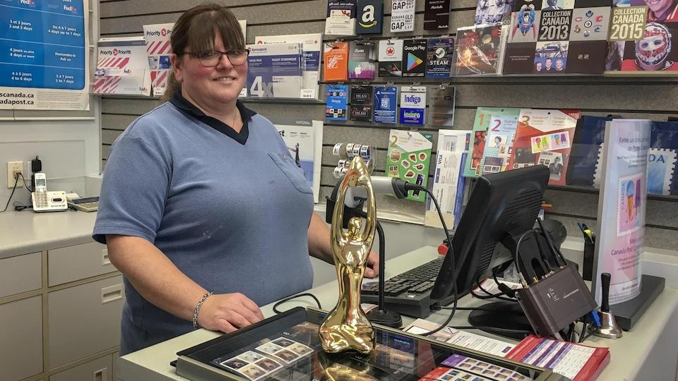 Une femme derrière un comptoir postal avec un trophée.