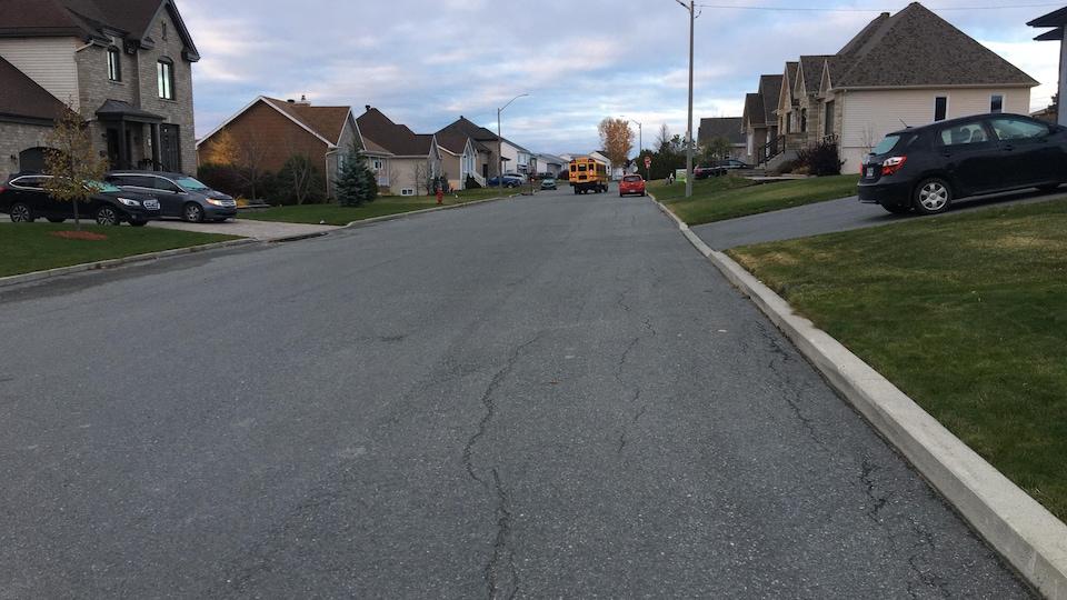 Plusieurs maisons sont construites sur la rue qui n'a aucun trottoir ou démarcation sur le sol pour les piétons ou cyclistes.