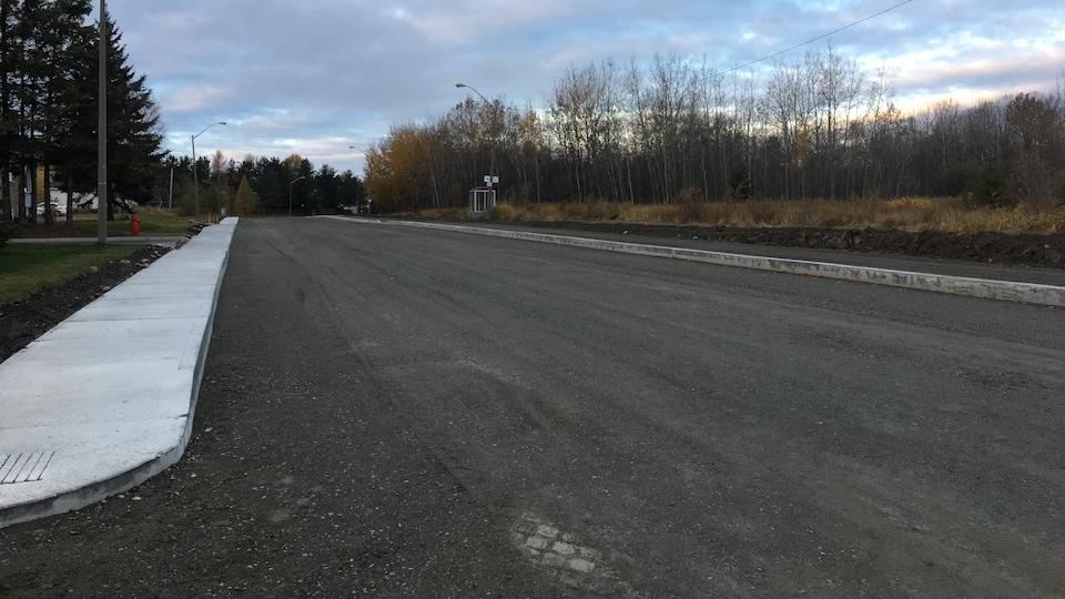 L'asphalte n'est pas encore en place, mais le trottoir est nouvellement aménagé.