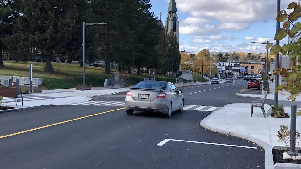Une voiture circule sur une rue nouvellement revampée. Les gens peuvent circuler sur un passage pour piétons afin de traverser la rue.