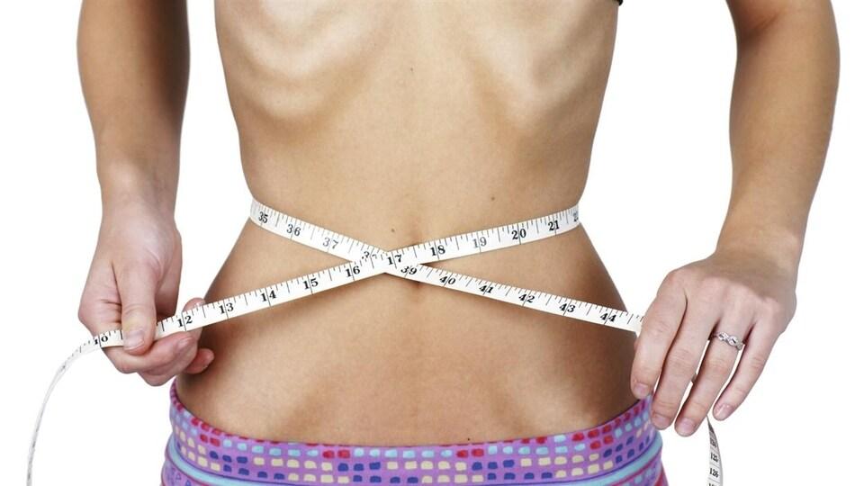 Une fille mesure son tour de taille.