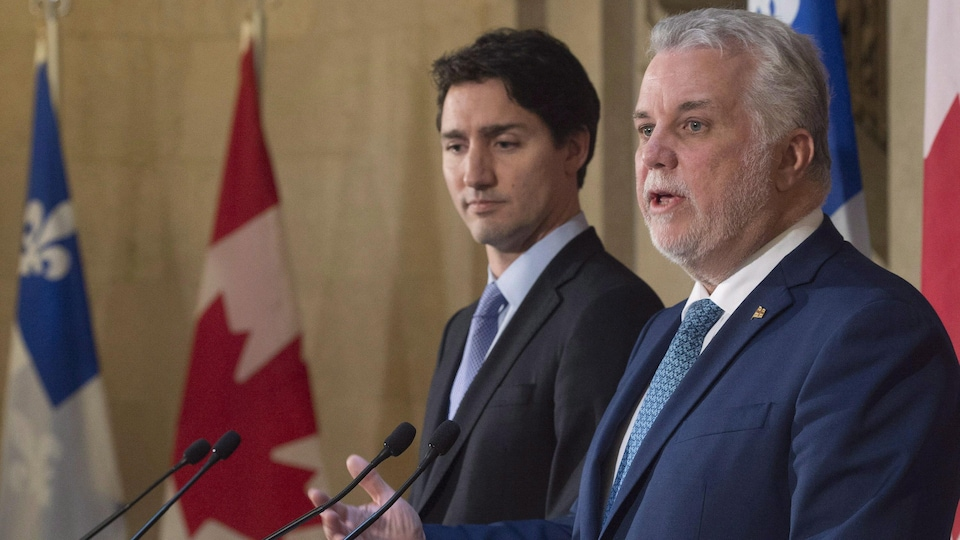Un homme aux cheveux blancs et ayant une petite barbe blanche répond à une question. Un autre homme plus jeune se tient derrière lui. Ils sont entourés de drapeaux du Québec et du Canada,