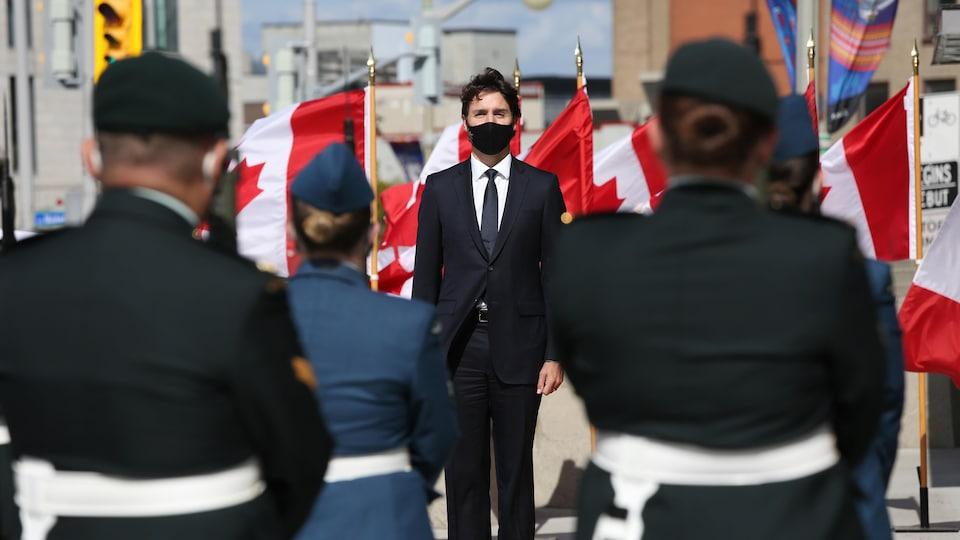 M. Trudeau, masqué, debout devant l'unifolié, fait face à des militaires.