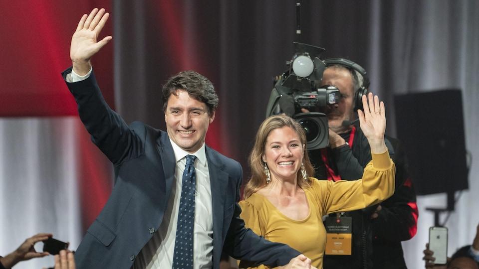 Justin Trudeau et Sophie Grégoire souriant et saluant les militants libéraux au Palais des congrès, à Montréal.