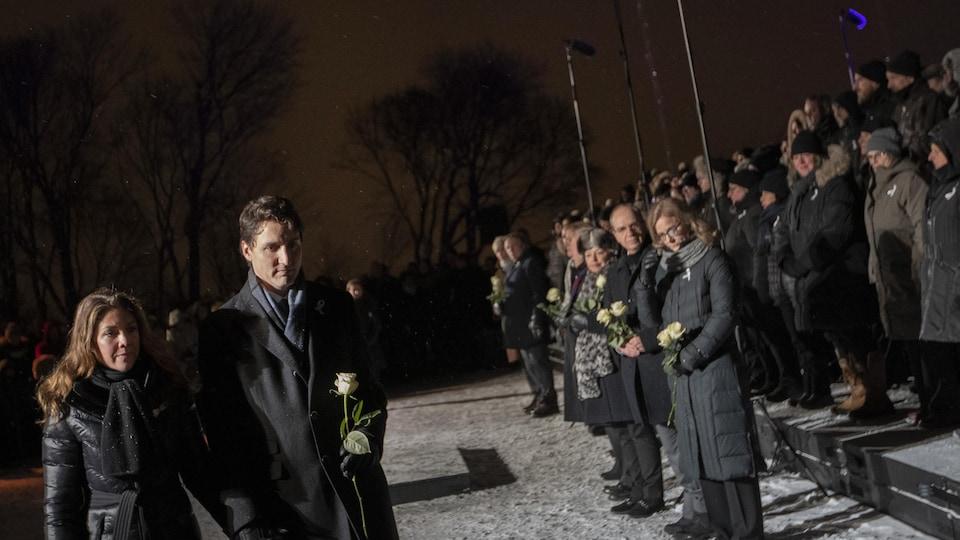 Justin Trudeau et son épouse marchent devant un groupe de personnes qui se recueillent.