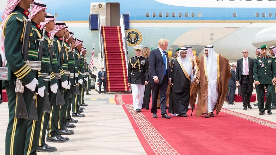 Donald Trump marche sur un tapis rouge avec le roi Salmane lors de son arrivée à Riyad.