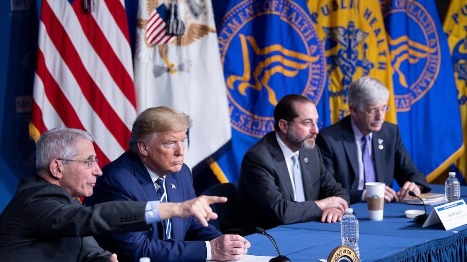 Donald Trump est entouré de quatre personnes. Tous sont assis devant une table de conférence.