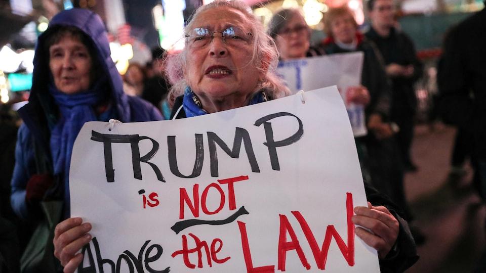 Une femme tient une banderole sur laquelle on peut lire «Trump n'est pas au-dessus de la loi».