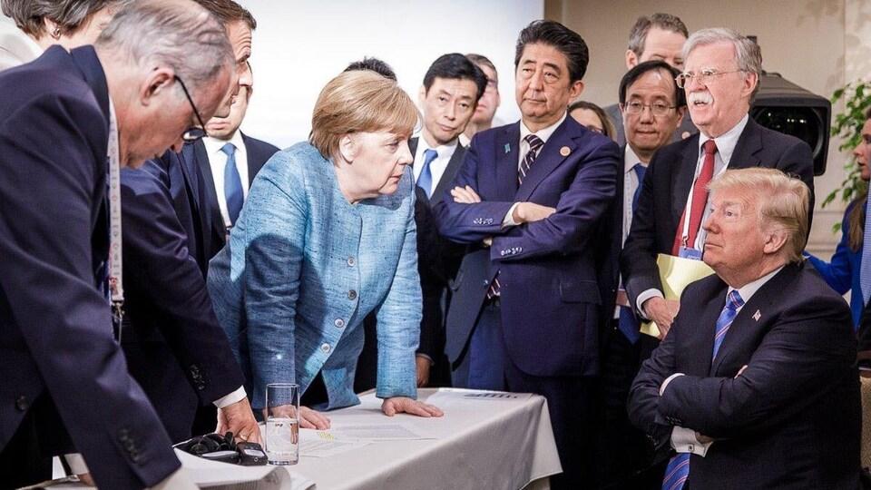 Donald Trump, assis, semble se faire gronder par Angela Merkel, debout devant lui.