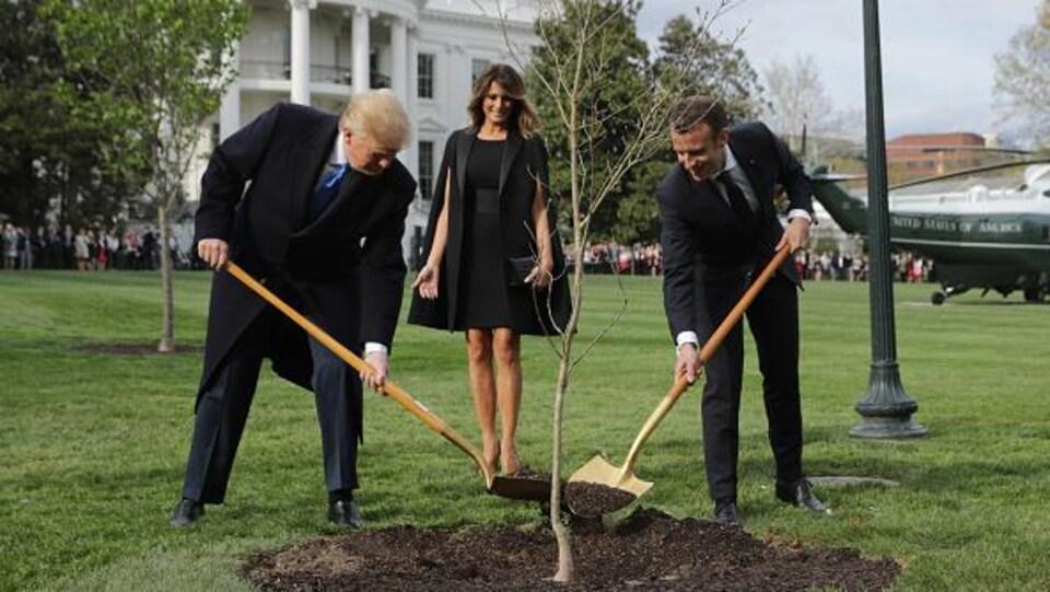 Donald Trump et Emmanuel Macron tiennent une pelle.